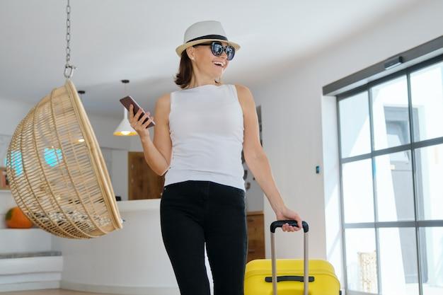 Reife schöne frau mit koffer in der lobby des modernen spa-resort-hotels.