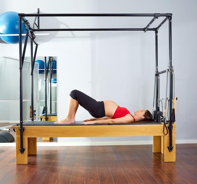 Reife schulterbrücke der schwangeren frau pilates