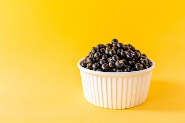 Reife schwarze johannisbeere oder blaubeeren in einer kleinen weißen schale auf gelb