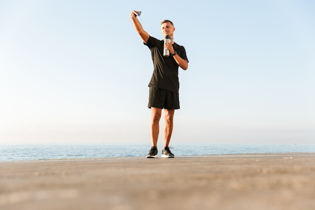 Reife sportler machen ein selfie mit einer flasche wasser am strand.