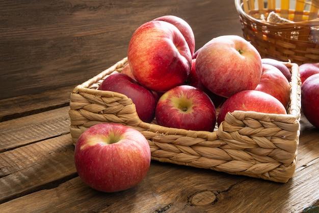 Reife süße äpfel liegen in einem korb auf einem hölzernen hintergrund.