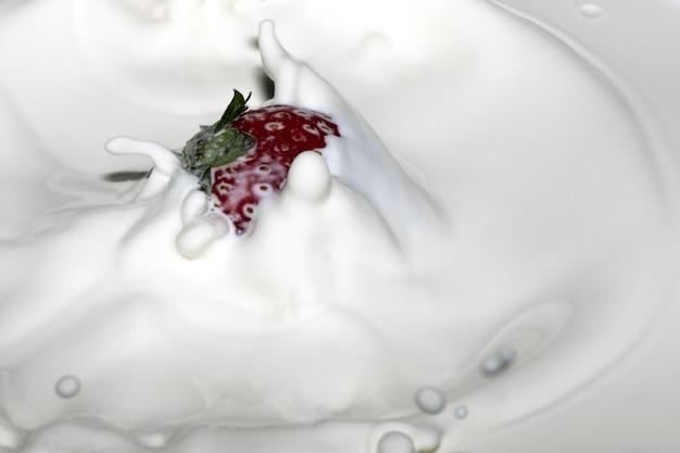 Reife süße frische erdbeere in sahne mit spritzern und blasen nahaufnahme