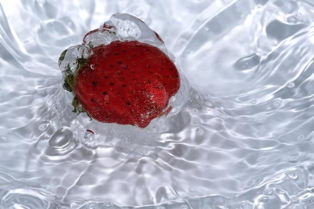 Reife süße frische erdbeere wird in sauberem kaltem wasser mit spritzern und blasen in nahaufnahme gewaschen