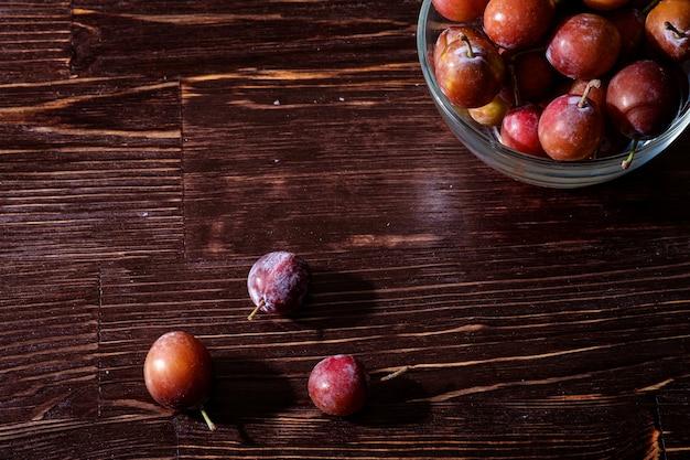 Reife süße pflaumenfrüchte in glasschale nahe mit verstreuten pflaumen auf dunklem launischem holztisch