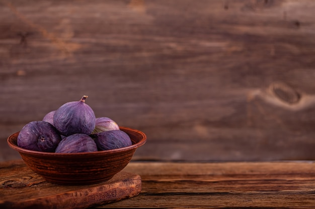 Reife süße violette feigen in der weinleseschüssel, holztisch, konzept der bonbons des strengen vegetariers