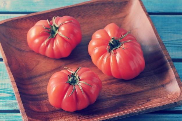 Reife tomate mit drei rottönen mit grünem stiel auf einer platte