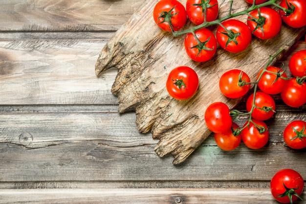 Reife tomaten auf schneidebrett auf holztisch