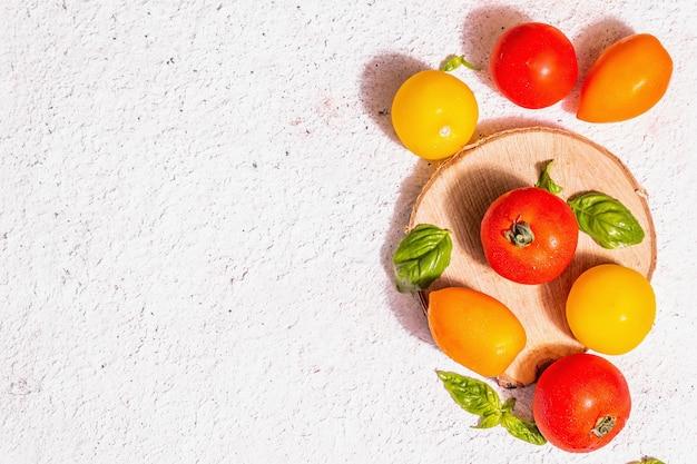 Reife tomaten des sortiments mit frischen basilikumblättern. neue ernte, ganzes und halbiertes gemüse, trendiges hartes licht, dunkle schatten. weißer kitthintergrund, draufsicht