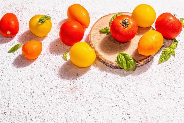 Reife tomaten des sortiments mit frischen basilikumblättern. neue ernte, ganzes und halbiertes gemüse, trendiges hartes licht, dunkle schatten. weißer kitthintergrund, platz für text