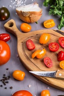 Reife tomaten für das kochen des gemüsetellers auf einem grau