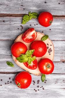 Reife tomaten mit frischen basilikumblättern, schwarzem salz und pfefferkörnern. ganzes und geschnittenes halbes gemüse, alter holzbretthintergrund, draufsicht
