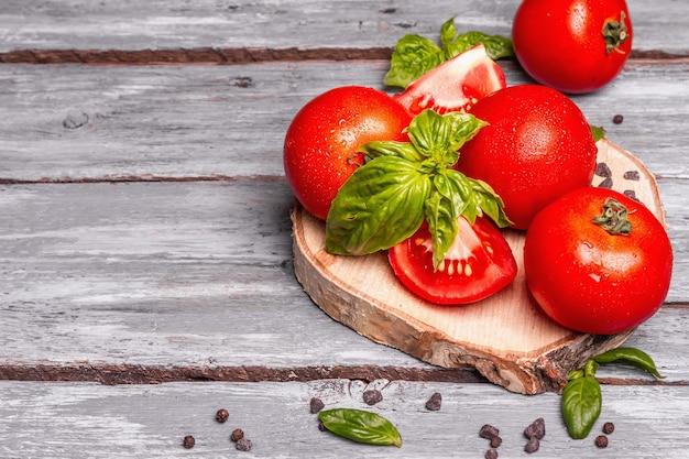 Reife tomaten mit frischen basilikumblättern, schwarzem salz und pfefferkörnern. ganzes und halb geschnittenes gemüse, alter holzbretthintergrund, kopierraum