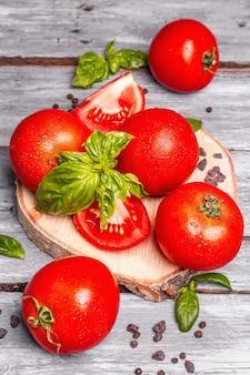 Reife tomaten mit frischen basilikumblättern, schwarzem salz und pfefferkörnern. ganzes und halb geschnittenes gemüse, alter holzbretthintergrund, nahaufnahme