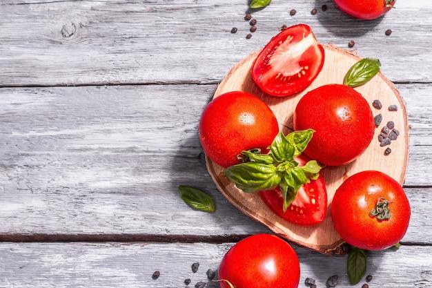 Reife tomaten mit frischen basilikumblättern, schwarzem salz und pfefferkörnern. ganzes und halb geschnittenes gemüse, trendiges hartes licht, dunkler schatten. alte holzbretter hintergrund, ansicht von oben