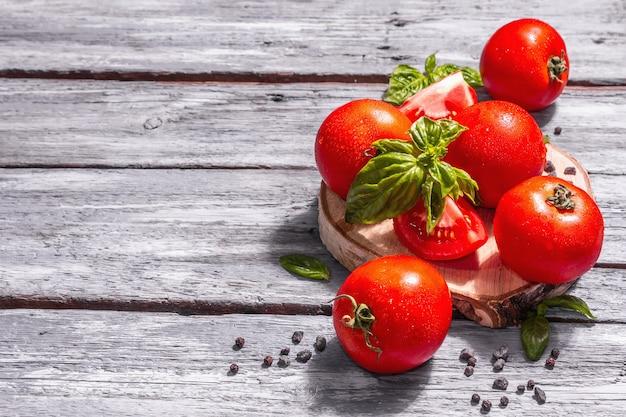 Reife tomaten mit frischen basilikumblättern, schwarzem salz und pfefferkörnern. ganzes und halb geschnittenes gemüse, trendiges hartes licht, dunkler schatten. alte holzbretter hintergrund, kopienraum