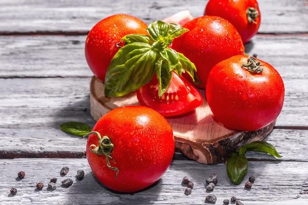 Reife tomaten mit frischen basilikumblättern, schwarzem salz und pfefferkörnern. ganzes und halb geschnittenes gemüse, trendiges hartes licht, dunkler schatten. alte holzbretter hintergrund, nahaufnahme