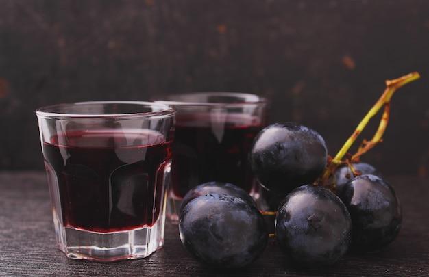 Reife trauben, rotwein und ein glas auf schwarzem hintergrund