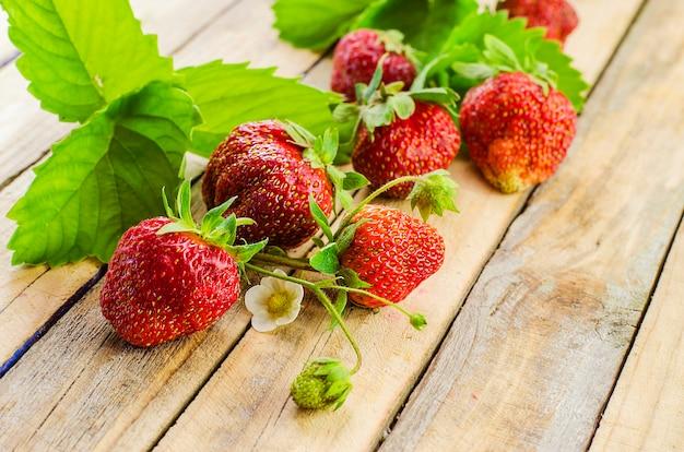 Reife und frische erdbeeren auf einer holzoberfläche