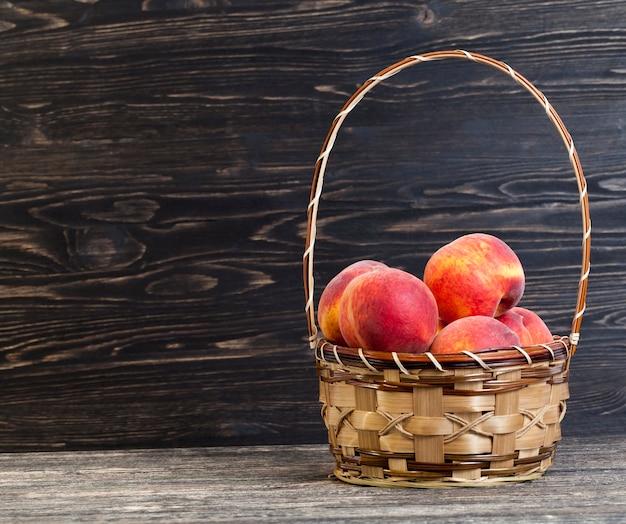 Reife und leckere pfirsiche in einem korb stehen auf einem schwarzen holztisch