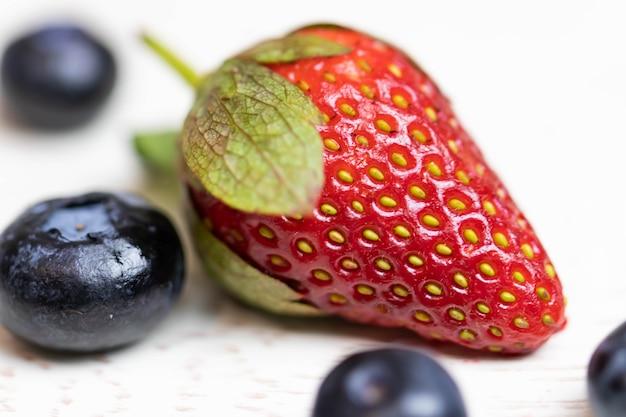 Reife und saftige erdbeeren und blaubeeren auf einem weißen hintergrund. gesundes essen.