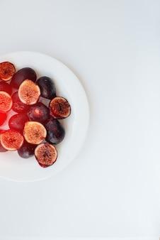 Reife und süße feigen geschnitten und in einem teller auf weißem hintergrund mit freiem platz angeordnet. obst und vegetarismus.