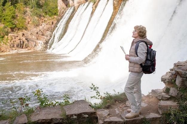 Reife wanderin mit rucksack und kartenführer, die an wasserfällen in natürlicher umgebung steht und den richtigen weg sucht