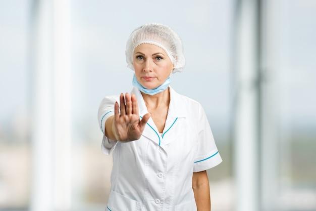 Reife weibliche chirurgin gestikuliert aufhören. zuversichtlich arzt frau show stop geste.
