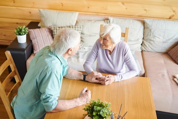 Reife weißhaarige frau, die ihren ehemann ansieht, während sie hört, was er während ihres gesprächs am tisch sagt