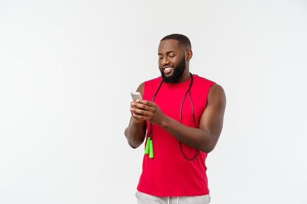 Reifen sie den geeigneten afroamerikanermann, der auf mobile simst und elastisches seil hält.