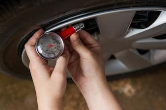 Reifendruckmesser: Hand hält Manometer zur Kontrolle des Luftdrucks für Autoreifen. Sicheres Fahren.