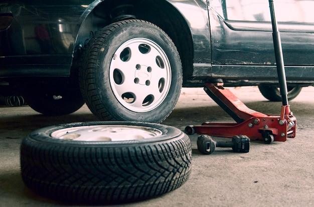 Reifenwerkstatt und altes rad auf dem auto wechseln