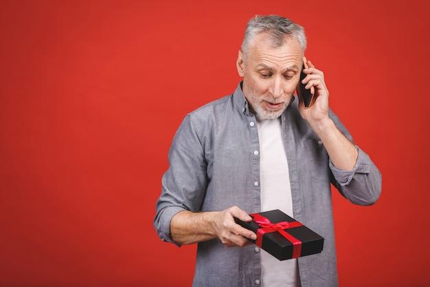 Reifer älterer mann, der ein geschenk mit rotem band als geschenk lokalisiert zeigt. telefon benutzen.