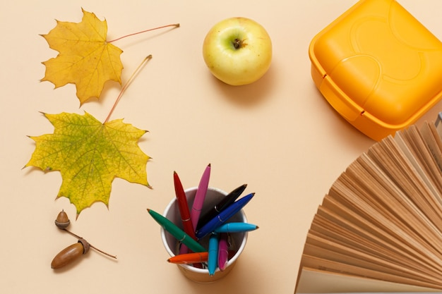 Reifer apfel, ein buch, eine plastik-lunchbox, stifte, trockene gelbe ahornblätter und eine eichel auf beigem hintergrund. ansicht von oben.