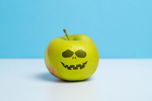 Reifer apfel mit einem bösen lächeln halloween-feiertag