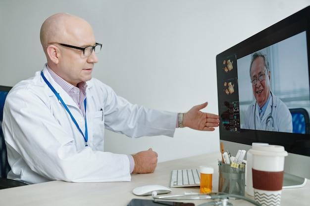 Reifer arzt, der an seinem arbeitsplatz sitzt und während der online-konferenz am computer mit seinem kollegen spricht
