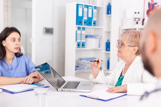 Reifer arzt, der während des treffens mit ihrem medizinischen personal über die patientendiagnose spricht. kliniktherapeut mit kollegen, die über krankheit, experten, spezialisten, kommunikation sprechen.