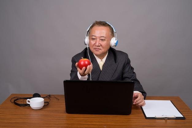 Reifer asiatischer geschäftsmann, der mit holztisch gegen grau sitzt