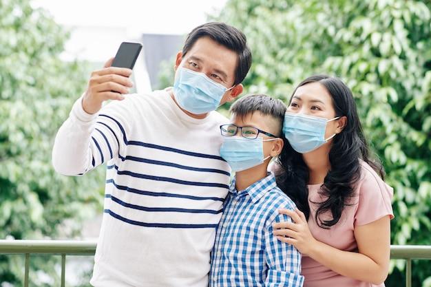 Reifer asiatischer mann, der medizinische maske wegen coronavirus-pandemie trägt und selfie mit frau und jugendlichem kind nimmt