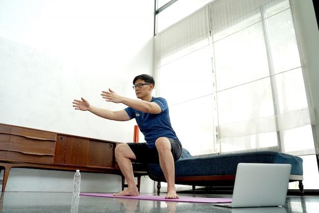 Reifer asiatischer mann, der übungen zu hause macht. training zu hause. soziale distanzierung.