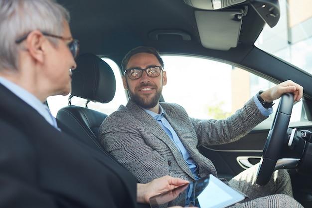 Reifer bärtiger geschäftsmann, der mit tablet-pc mit der geschäftsfrau spricht, während sie im auto sitzen