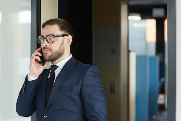Reifer bärtiger geschäftsmann in brille und im anzug, der auf handy spricht, während er entlang des bürokorridors geht