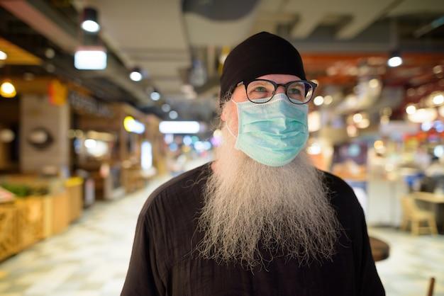 Reifer bärtiger hipster-mann, der mit maske zum schutz vor dem ausbruch des koronavirus im einkaufszentrum denkt