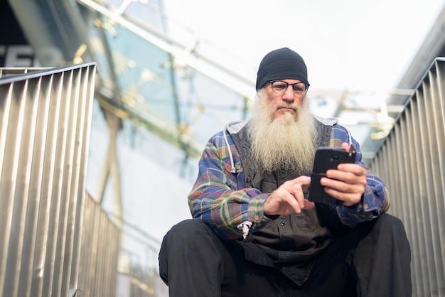 Reifer bärtiger hipster-mann, der telefon beim sitzen am steg in der stadt verwendet