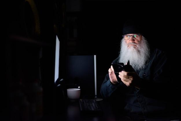 Reifer bärtiger hipster-mann, der telefon benutzt, während er spät in der nacht im dunkeln überstunden zu hause macht