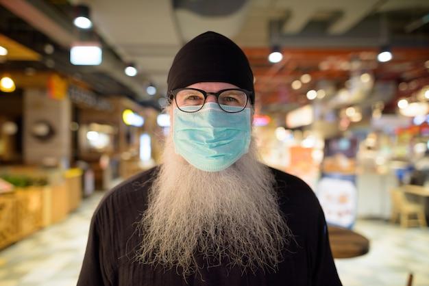 Reifer bärtiger hipster-mann mit maske zum schutz vor dem ausbruch des koronavirus im einkaufszentrum