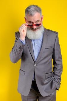 Reifer bärtiger hübscher mann des studioporträts im grauen geschäftsanzug, der kamera, arbeitsberufslebensstil, gelben hintergrund sucht.