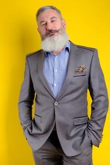 Reifer bärtiger hübscher mann des studioporträts im grauen geschäftsanzug