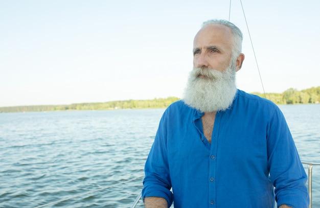 Reifer bärtiger mann, der am steuer der yacht draußen am see steht, lenkt, lächelt. l.