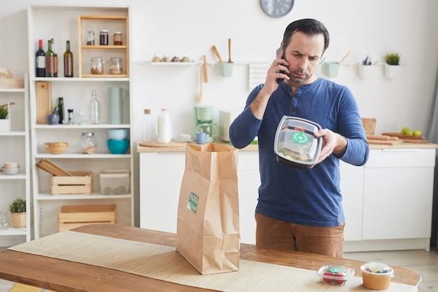 Reifer bärtiger mann, der durch smartphone spricht, während lebensmittelauslieferungsbeutel im innenraum der küche auspackt