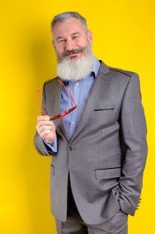 Reifer bärtiger mann des studioporträts im grauen geschäftsanzug, der kamera, arbeitsberufslebensstil, gelben hintergrund sucht.